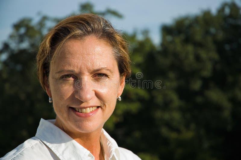 Het Glimlachen van de Vrouw van de middenLeeftijd stock fotografie