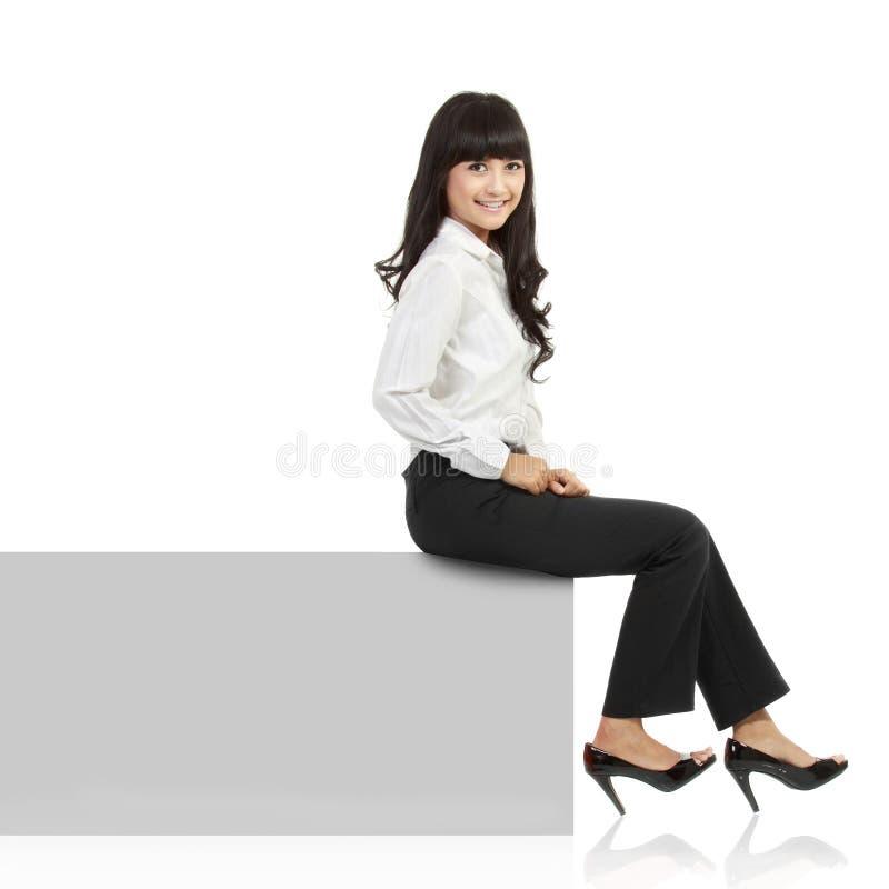 Het glimlachen van de vrouw zitting op horizontale bannerrand royalty-vrije stock foto