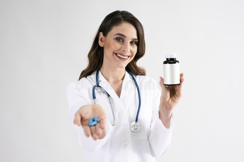 Het glimlachen van de vrouwelijke fles van de artsenholding van pillen stock afbeeldingen