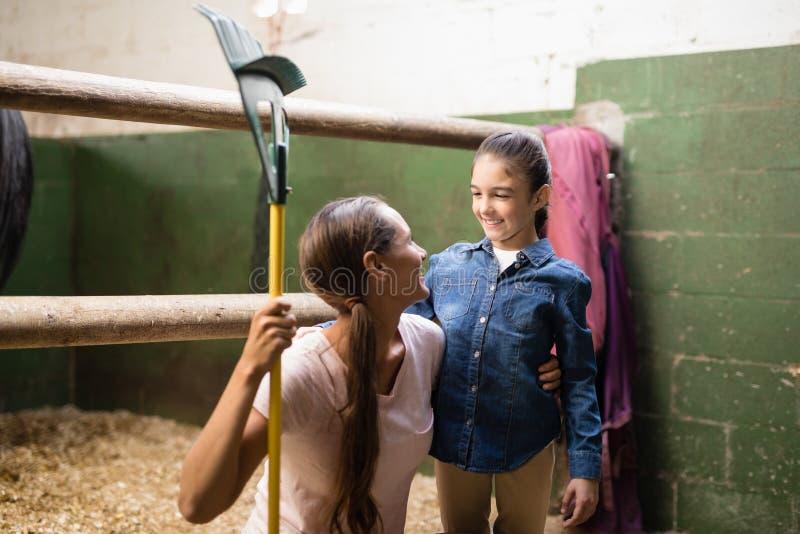Het glimlachen van de vrouwelijke hark van de jockeyholding terwijl het spreken aan zuster royalty-vrije stock afbeeldingen