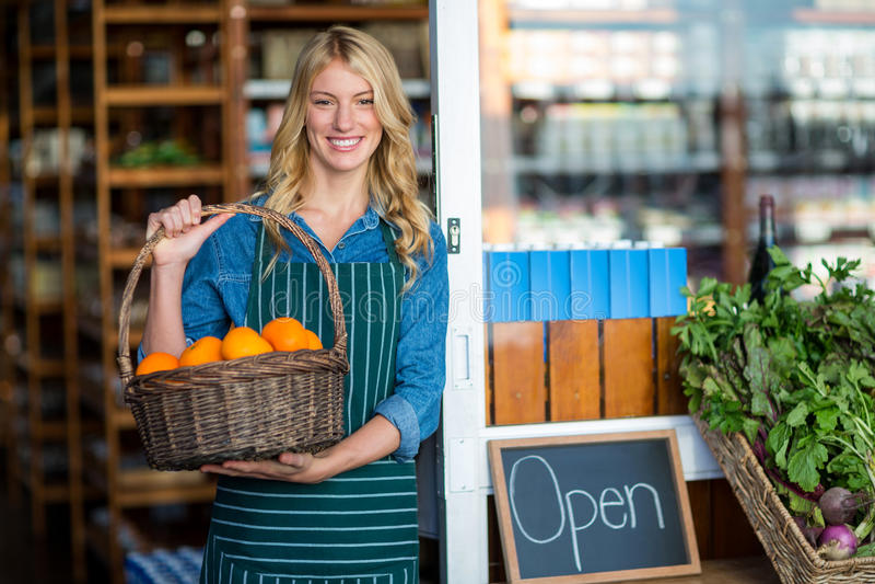 Het glimlachen van de vrouwelijke mand van de personeelsholding fruit in supermarkt royalty-vrije stock afbeeldingen
