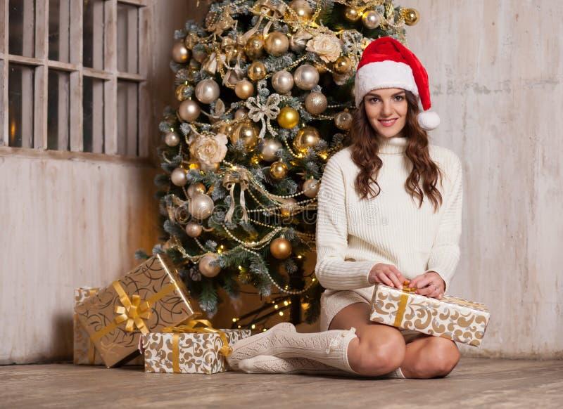 Het glimlachen van doos van de vrouwen de uitpakkende gift dichtbij Kerstboom royalty-vrije stock afbeeldingen