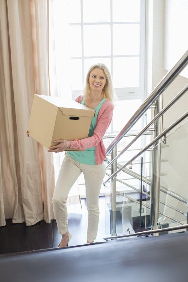 Het glimlachen van doos van het vrouwen de dragende karton terwijl zich het bewegen op stappen bij nieuw huis royalty-vrije stock foto's