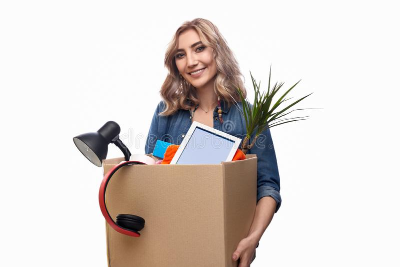 Het glimlachen van doos van het vrouwen de dragende karton met bezittingen stock afbeeldingen