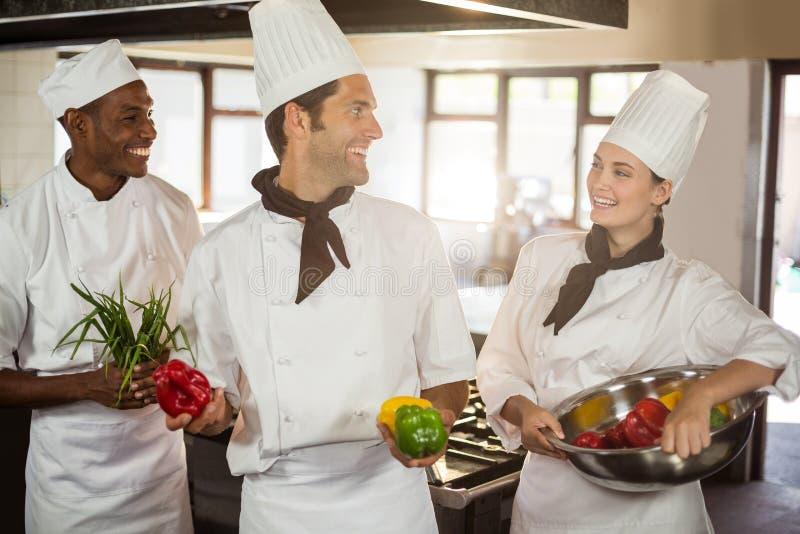 Het glimlachen van drie chef-koks die groenten houden stock afbeeldingen