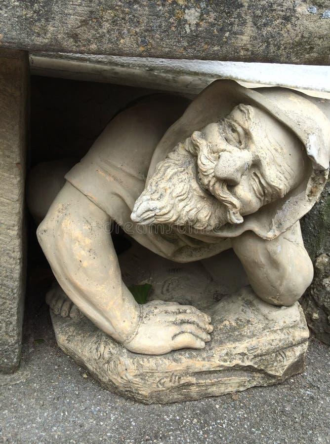 Het glimlachen van dwergstandbeeld onder een blok van steen royalty-vrije stock afbeelding