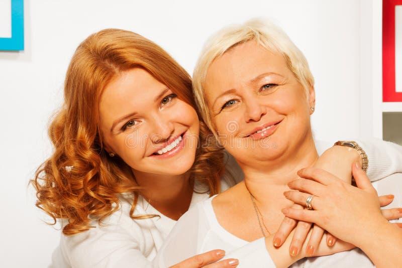 Het glimlachen van en het koesteren van dochter met oude moeder royalty-vrije stock foto