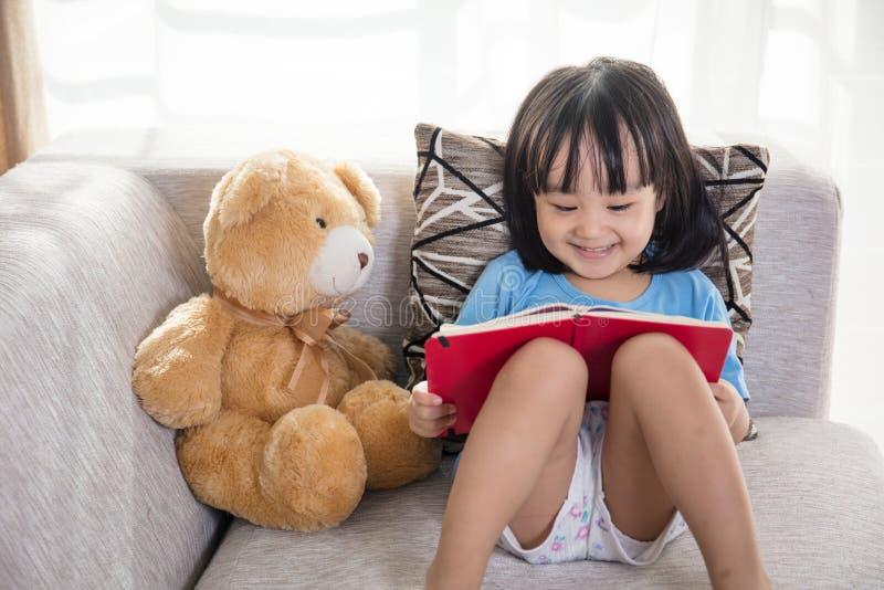 Het glimlachen van het Aziatische Chinese boek van de meisjelezing met teddybeer royalty-vrije stock afbeelding