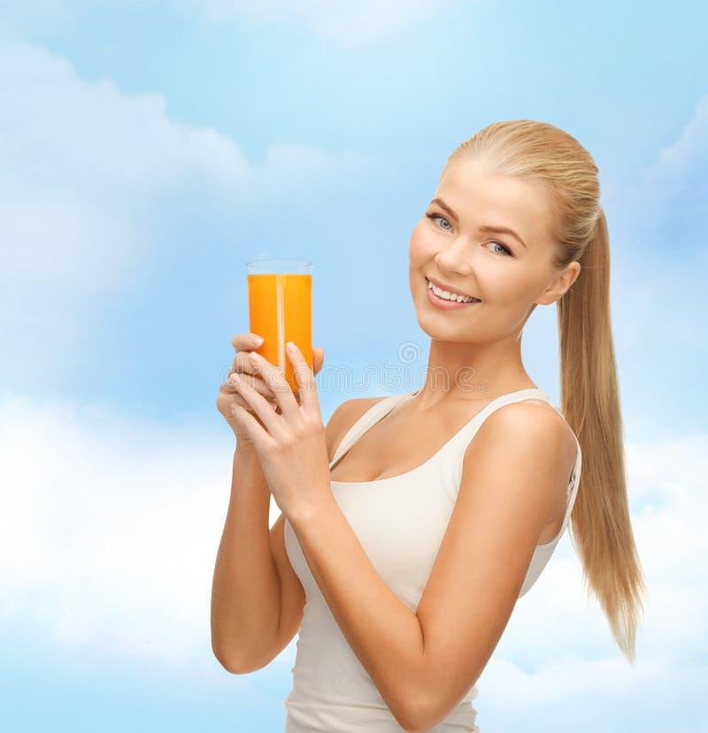 Het glimlachen van het glas van de vrouwenholding jus d'orange stock afbeelding