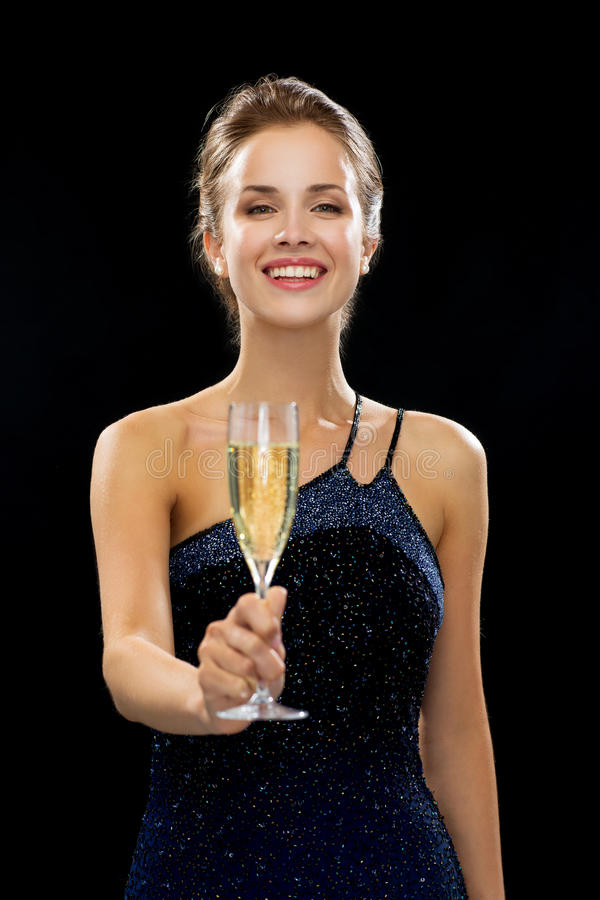Het glimlachen van het glas van de vrouwenholding mousserende wijn stock foto