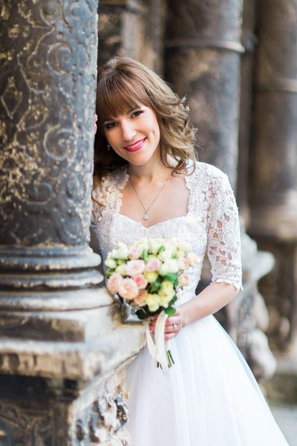 Het glimlachen van het huwelijksboeket van de bruidholding op achtergrond van de oude bouw met kolommen, close-up royalty-vrije stock foto