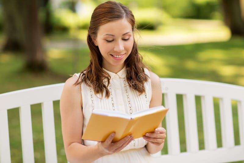 Het glimlachen van het jonge boek van de vrouwenlezing bij de zomerpark stock afbeelding