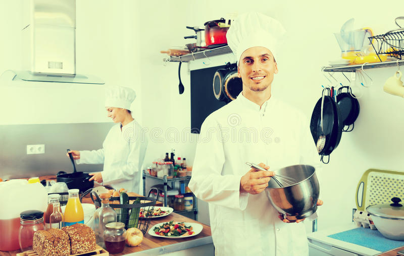 Het glimlachen van het kokende voedsel van de jonge mensenchef-kok bij keuken stock afbeelding