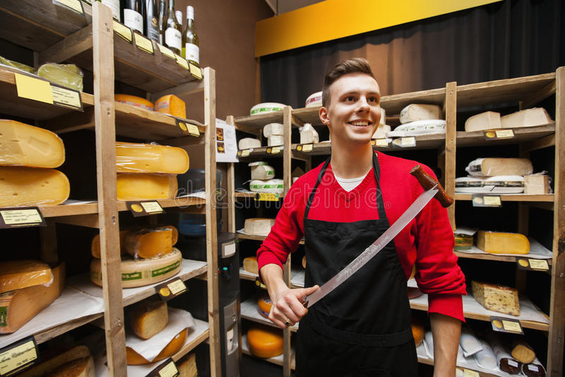 Het glimlachen van het mannelijke mes van de winkelbediendeholding in kaasopslag royalty-vrije stock fotografie