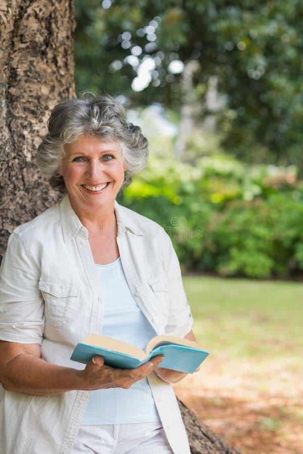 Het glimlachen van het rijpe boek die van de vrouwenlezing op boomboomstam leunen stock foto's