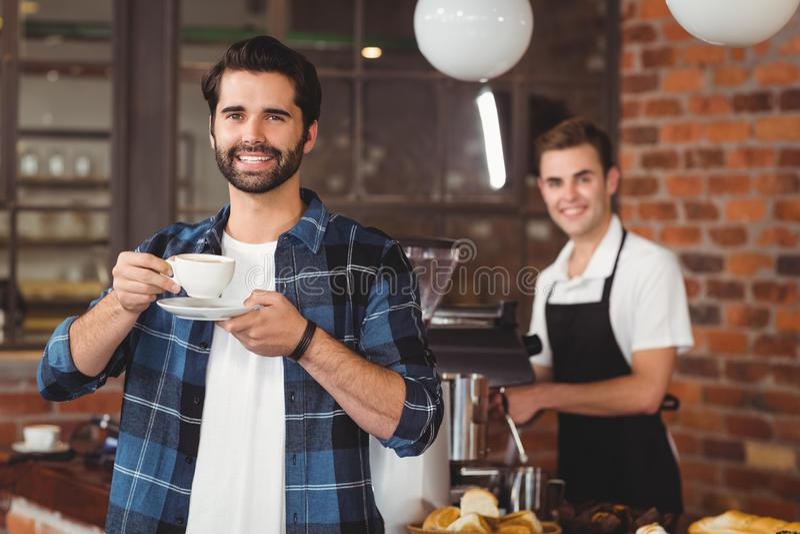 Het glimlachen van hipster het drinken koffie voor barista royalty-vrije stock fotografie