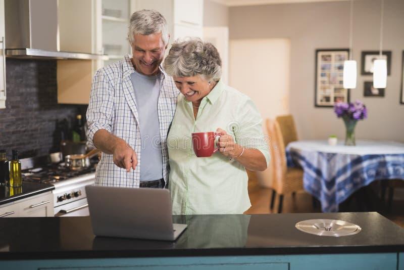 Het glimlachen van hogere paar het letten op laptop terwijl status in keuken stock afbeeldingen