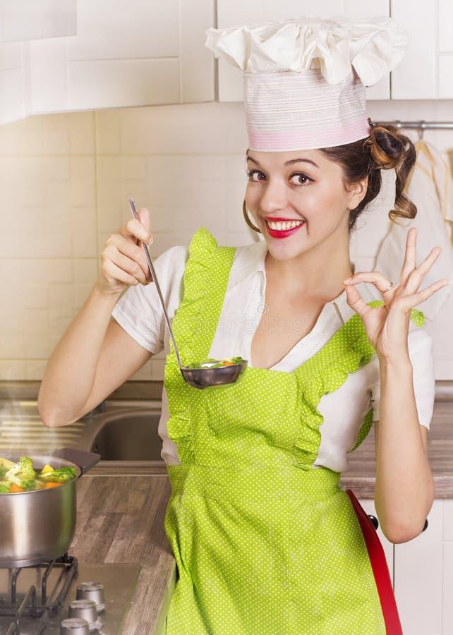 Het glimlachen van huisvrouwen proevende soep met gietlepel stock foto's