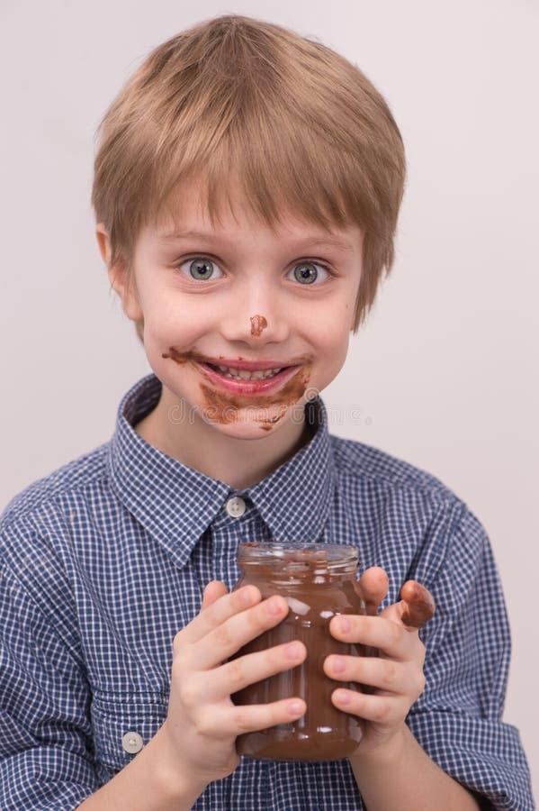 Het glimlachen van jong geitje die chocolade van kruik eten royalty-vrije stock fotografie