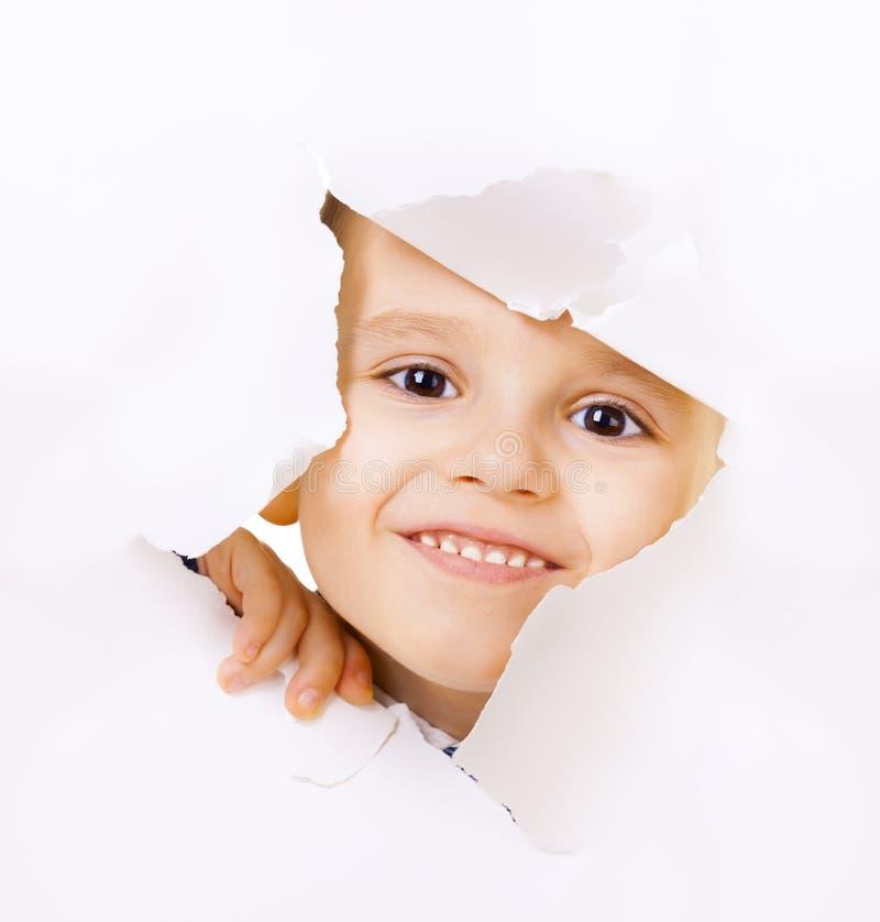 Het glimlachen van jong geitje die uit een gat kijken royalty-vrije stock foto's