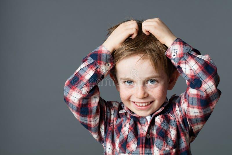Het glimlachen van jong jongens krassend haar voor hoofdluizen of allergieën royalty-vrije stock afbeeldingen