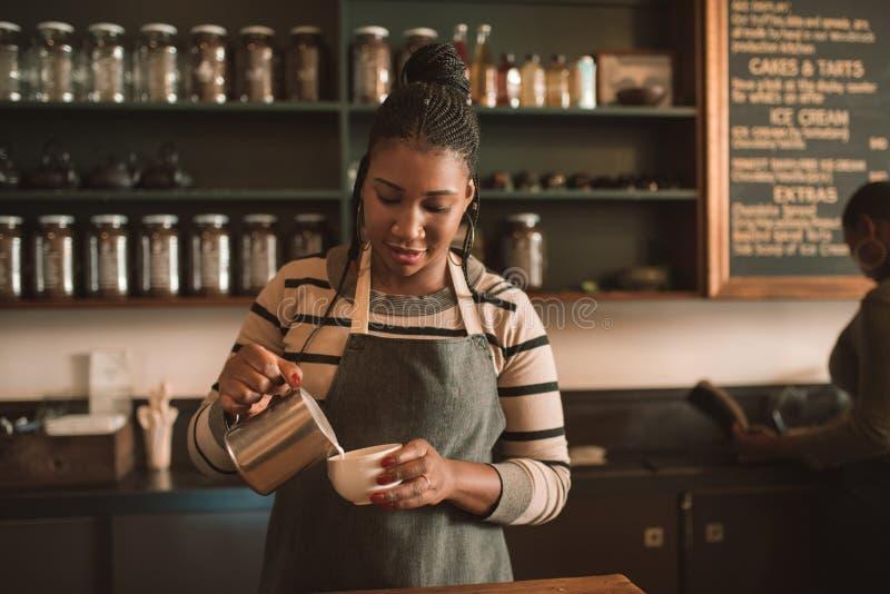 Het glimlachen van jonge Afrikaanse barista gietende melk in een cappuccino stock foto