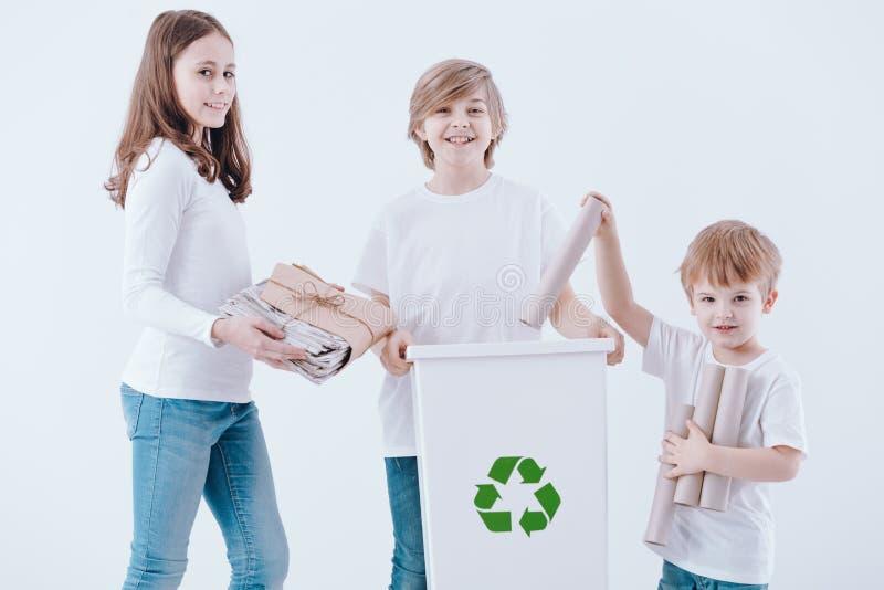 Het glimlachen van jonge geitjes die document afval afzonderen stock foto
