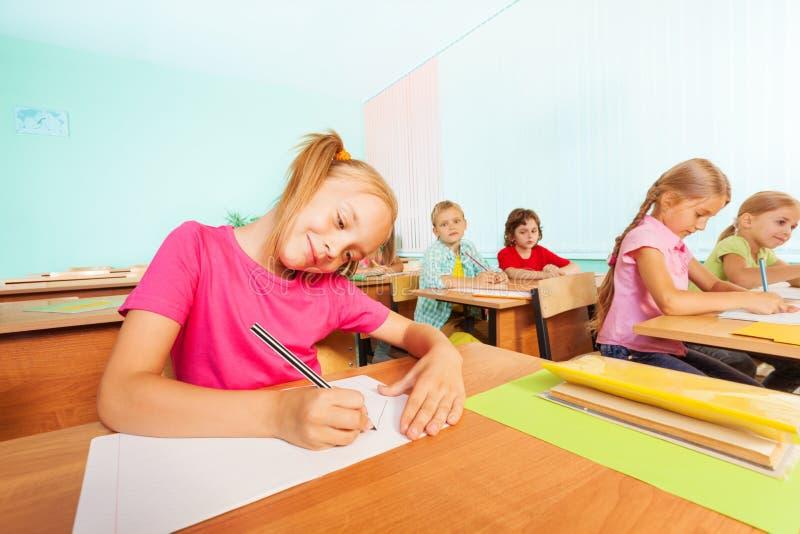 Het glimlachen van jonge geitjes die in klaslokaal tijdens les schrijven royalty-vrije stock foto's