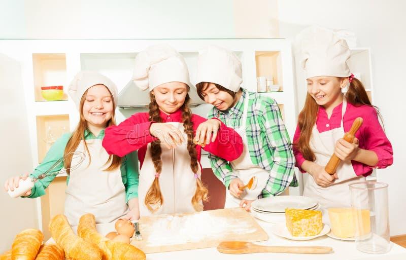 Het glimlachen van jonge geitjes in het maken van de kok eenvormig bakkerijdeeg stock afbeeldingen