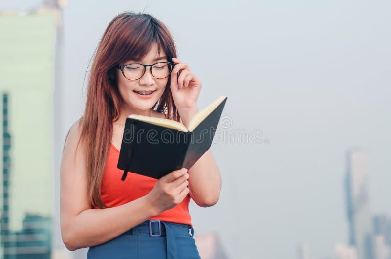 Het glimlachen van Jonge mooie Aziatische vrouwen in glazen leest boek in de zomerstad stock fotografie