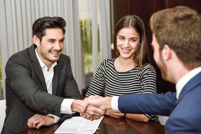 Het glimlachen van jonge paar het schudden handen met een verzekeringsagent