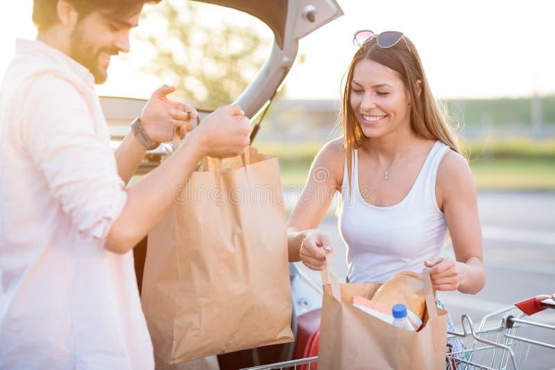 Het glimlachen van jonge paar het leegmaken kruidenierswinkelzakken van boodschappenwagentje stock afbeelding