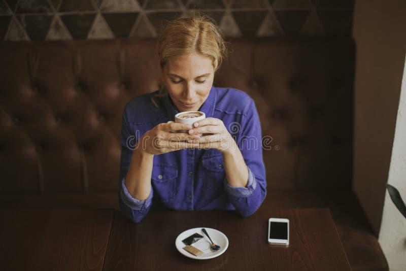 Het glimlachen van jonge vrouw het drinken koffie bij koffie stock afbeeldingen