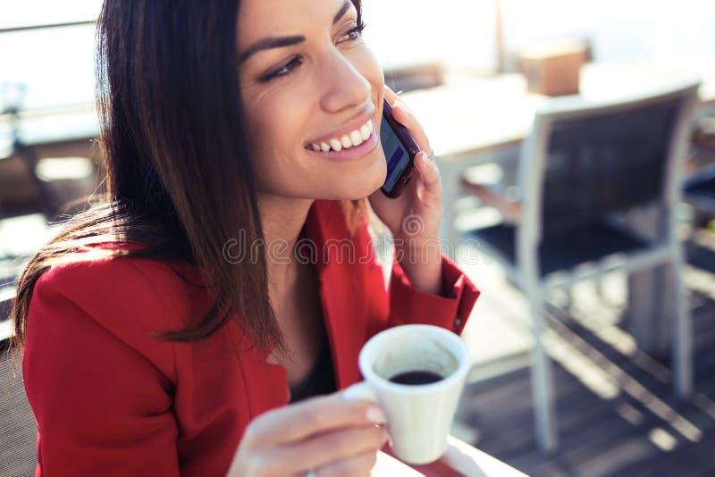 Het glimlachen van jonge vrouw het drinken koffie terwijl het texting met haar mobiele telefoon wodden lijst in het terras van ee stock foto