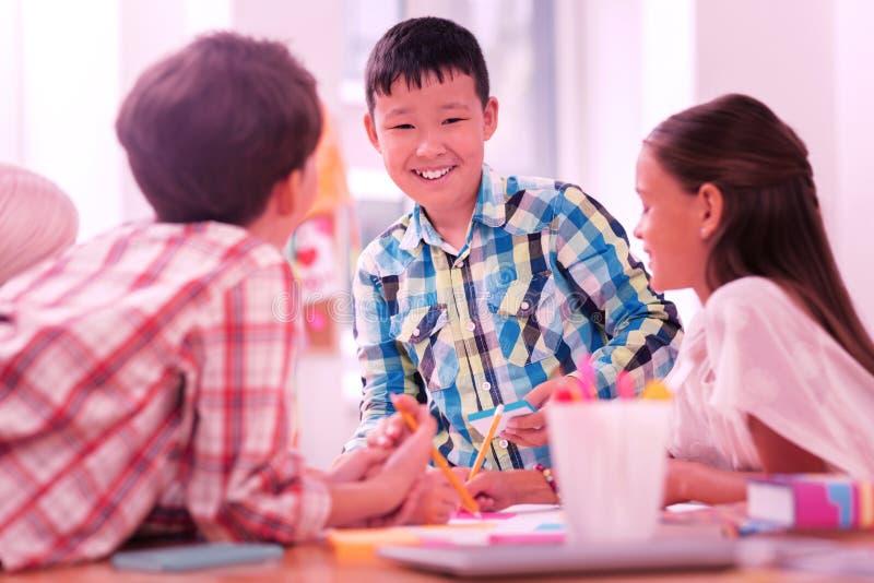 Het glimlachen van jongenstekening met zijn vrienden in klasse stock foto's