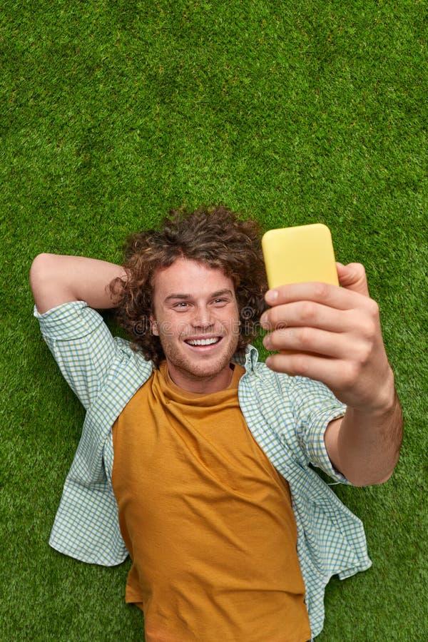 Het glimlachen van kerel die selfie op gras nemen royalty-vrije stock afbeelding