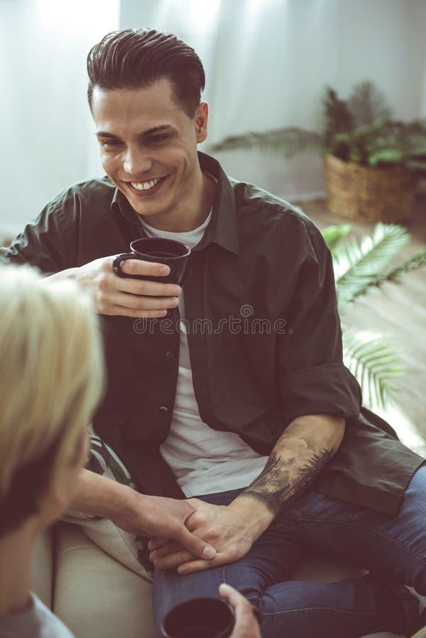 Het glimlachen van kerel die vriend bekijken en het houden van zijn hand royalty-vrije stock foto's