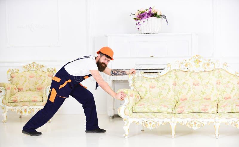 Het glimlachen van kerel met snor bewegend meubilair in nieuwe vlakte De gebaarde uitstekende bank van de arbeidersverhuizing in  royalty-vrije stock fotografie