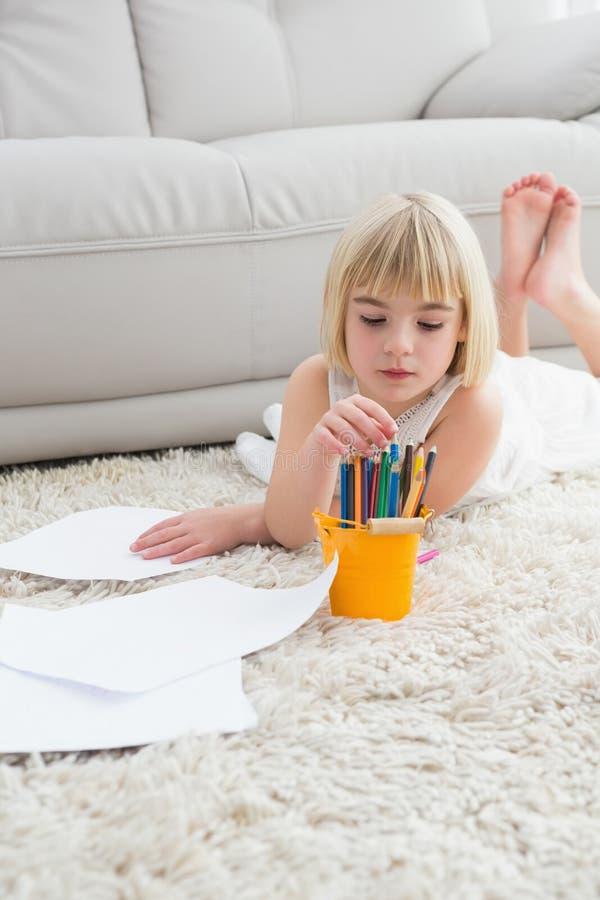 Het glimlachen van litlle meisjestekening die op de vloer liggen royalty-vrije stock afbeeldingen