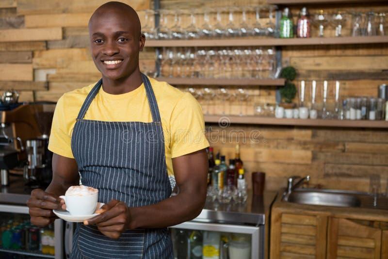 Het glimlachen van mannelijke de koffiekop van de baristaholding in koffie stock afbeelding