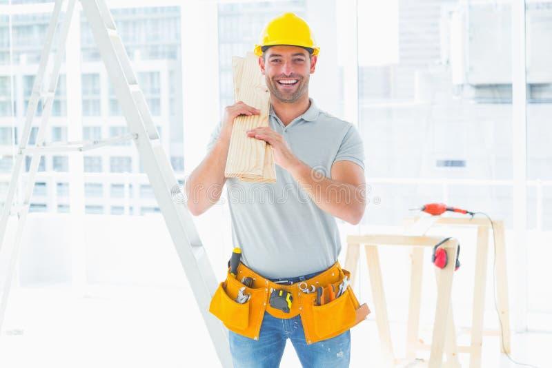 Het glimlachen van manusje van alles dragende planken in de bouw royalty-vrije stock fotografie