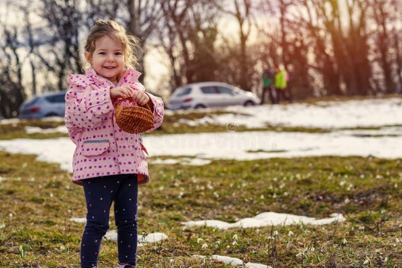 Het glimlachen van meisje het plukken sneeuwklokjebloemen in de lentebos royalty-vrije stock fotografie