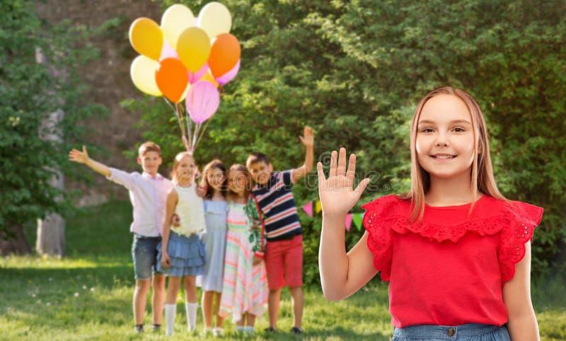 Het glimlachen van meisjes golvende hand bij verjaardagspartij in park stock foto's