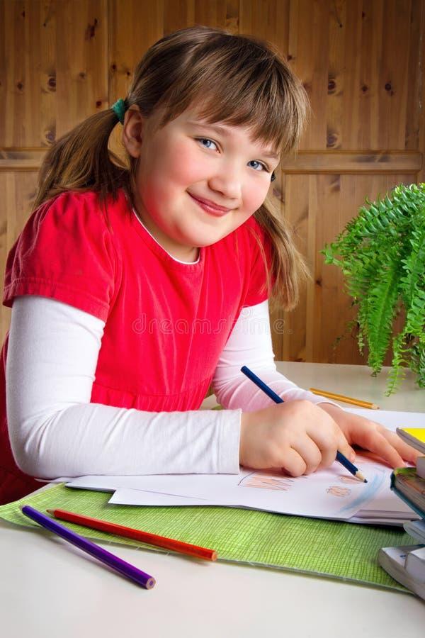 Het glimlachen van meisjestekening bij haar bureau stock afbeeldingen