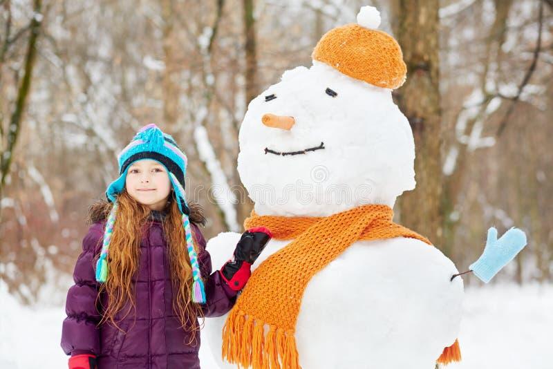 Het glimlachen van meisjestribunes naast sneeuwman in oranje hoed en sjaal stock fotografie