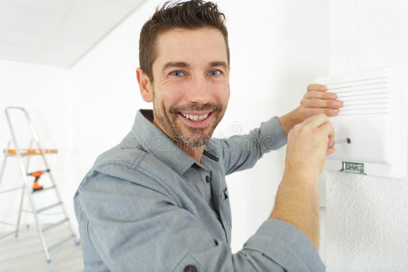 Het glimlachen van Mens het Aanpassen Thermostaat op Huis Verwarmingssysteem stock foto's