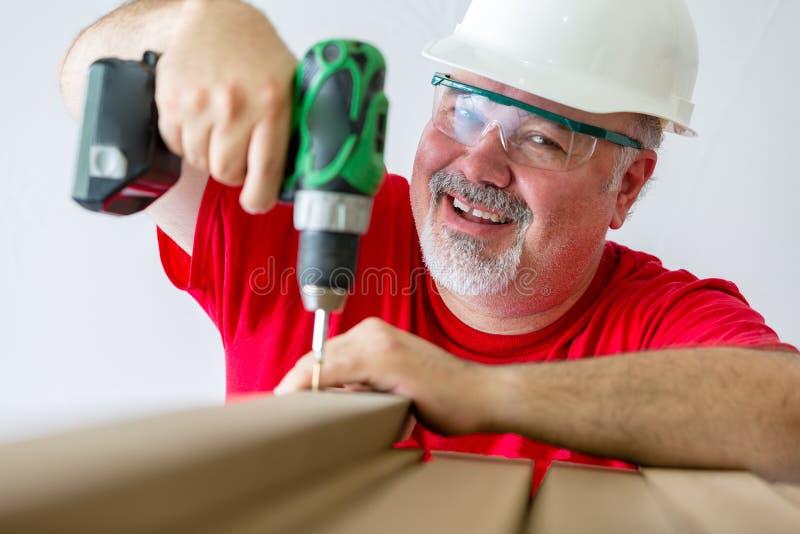 Het glimlachen van mens het assembleren hout met boor-aandrijving stock fotografie