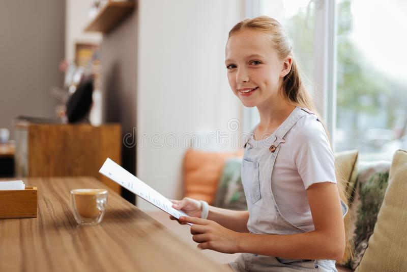 Het glimlachen van het menu van de tienerholding in haar handen royalty-vrije stock afbeeldingen
