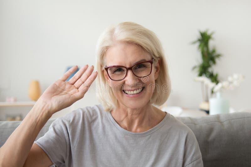 Het glimlachen van midden oude vrouwen golvende hand die camera, portrai bekijken stock foto