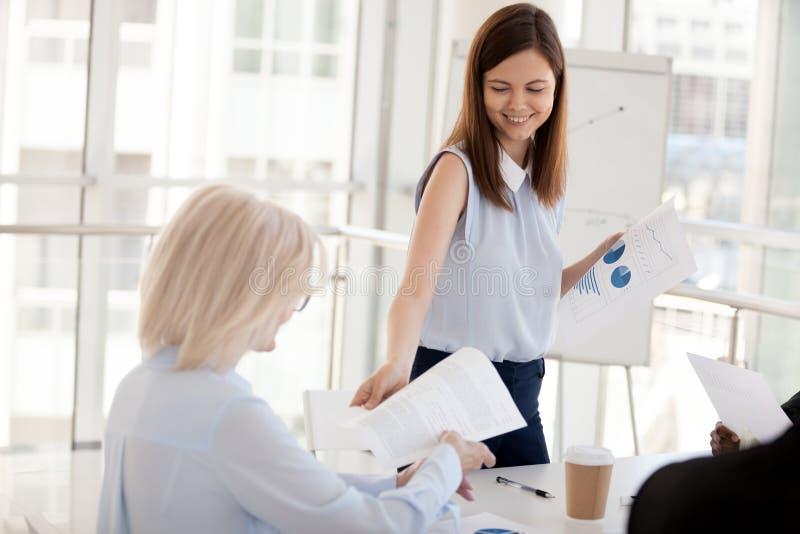 Het glimlachen van millennial folders van het mentoraandeel aan werknemers bij briefin royalty-vrije stock foto